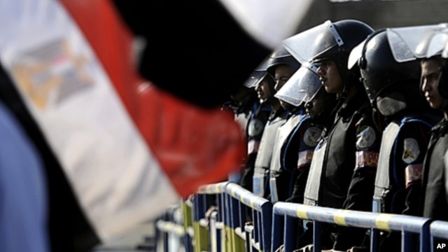 Egyptian anti-riot police stand by a national flag as the trial of former President Hosni Mubarak resumes at the Police Academy on the outskirts of Cairo, December 28, 2011.