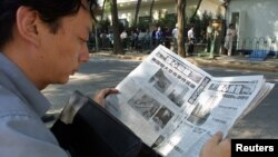 FILE - A Chinese visa applicant reads a Beijing newspaper as he waits outside the U.S. Embassy.