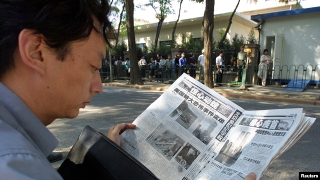FILE - A Chinese visa applicant reads a Beijing newspaper as he waits outside the U.S. Embassy compound.