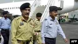FILE - Lt. General Shahid Aziz (foreground, left) walks with military officials at Allama Iqbal International Airport in Lahore, Pakistan, March 25, 2004.