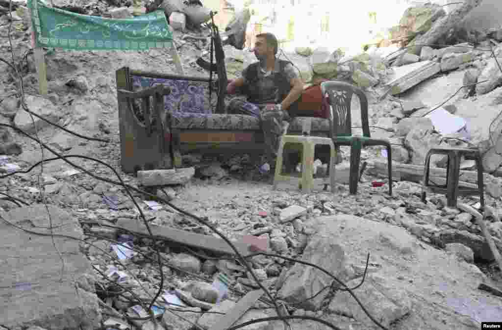 A Free Syrian Army fighter sits on a sofa along a street in Aleppo's Salaheddine neighbourhood, July 30, 2013.