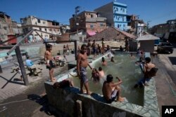 FILE - Children play in a pool that has no system to replace the water in Rio de Janeiro, Brazil, Aug. 13, 2015. Brazil is among the world's largest economies, but lags in access to water and sanitation. Rapid urban growth in recent decades, poor planning, political infighting and economic instability are largely to blame, experts say.
