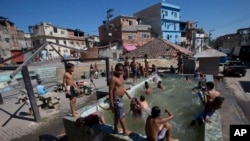 FILE - Children play in a pool that has no system to replace the water in Rio de Janeiro, Brazil, Aug. 13, 2015. Brazil is among the world's largest economies, but lags in access to water and sanitation. Rapid urban growth in recent decades, poor planning