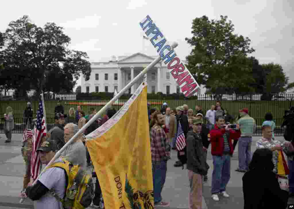 """Un hombre transporta una pancarta reclamando """"Impugnar a Obama"""" durante las protestas frente a la Casa Blanca en Washington."""