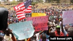 Supporters of Kenya's Opposition party Coalition for Reforms and Democracy (CORD), hold up banners and the US flag ahead of a CORD rally at Uhuru Park, Nairobi, Kenya, Wednesday, Sept. 23, 2015, in solidarity with striking teachers.