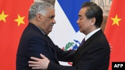 Dominican Republic Foreign Minister Miguel Vargas (L) embraces China's Foreign Minister Wang Yi after a signing ceremony where they formally established relations, in Beijing, May 1, 2018.
