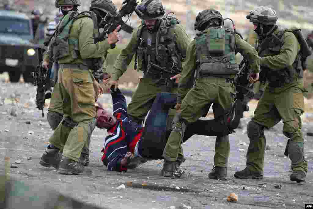 Israeli soldiers detain a wounded Palestinian stone thrower after security forces infiltrated Palestinian demonstrations and shot at protesters during clashes in Beit El, on the outskirts of the West Bank city of Ramallah.
