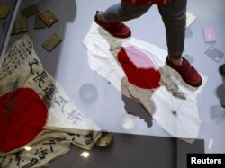 A visitor walks on a glass flooring above Japanese military flags seized by the Chinese People's Liberation Army (PLA) during World War II, at the Museum of the War of Chinese People's Resistance Against Japanese Aggression, in Beijing, China, Sept. 1, 20