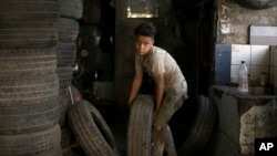 A boy carries a tire into the repair shop where he works in Cairo, Egypt, Wednesday, June 12, 2019. According to UN figures, 152 million children worldwide are working in almost every sector, with seven out of every ten children working in agriculture. (AP Photo/Maya Alleruzzo)