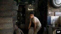 Một đứa bé đang làm việc ở một xưởng sửa xe ở Cairo, Ai Cập