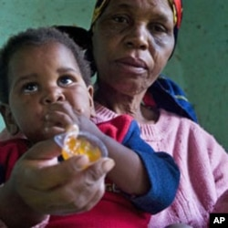 A child with HIV is given medication by a care-giver in Durban, South Africa Tuesday