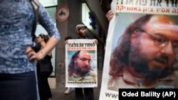FILE - Israeli protesters hold posters demanding the release of Jonathan Pollard, a Jewish American who was jailed in 1987 on charges of spying on the United States, as they stand outside the U.S. Embassy in Tel Aviv, June 19, 2011.