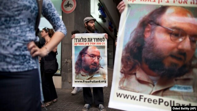 Israeli protesters hold posters demanding the release of Jonathan Pollard, a Jewish American who was jailed for life in 1987 on charges of spying on the United States, as they stand outside the U.S. embassy in Tel Aviv, Israel, Sunday, June 19, 2011.