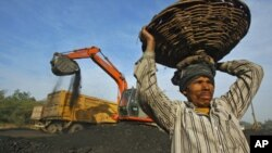 Seorang pekerja India mengangkat batu bara (foto: dok). Serikat buruh India menolak privatisasi perusahaan tambang batubara di sana.