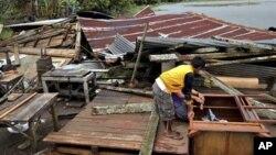 Seorang warga Filipina berdiri di atas puing-puing rumahnya yang hancur akibat hantaman topan Bopha yang melanda negeri itu (Foto: dok).
