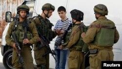 6月16日以色列军人在约旦河西岸搜查一名巴勒斯坦男孩