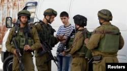 Tentara Israel mencari seorang remaja Palestina dalam operasi untuk mencari tiga remaja Israel yang diculik, di Hebron, Tepi Barat (16/6).