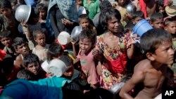 بنگلہ دیش کے ایک پناہ گزین کیمپ میں روہنگیا پناہ گزین خوراک ملنے کا انتظار کر رہے ہیں۔ فائل فوٹو