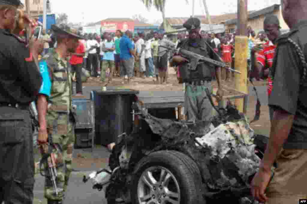 """Jami'in tsaro na duban motar da ta tarwatse da bam a kan hanyar """"Junction Road"""" a Kaduna a yau dinnan 04/08/2012."""
