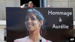 Un trabajador coloca un cartel con el retrato de Aurelie Chatelain en la alcaldía de Caudry, al norte de Francia. Se cree que la mujer fue asesinada por un presunto terrorista argelino que está capturado.