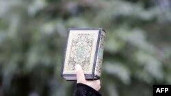 Suriyanın İstanbuldakı konsulluğu qarşısında etiraz nümayişinin iştirakçısı əlində Qur-an tutub