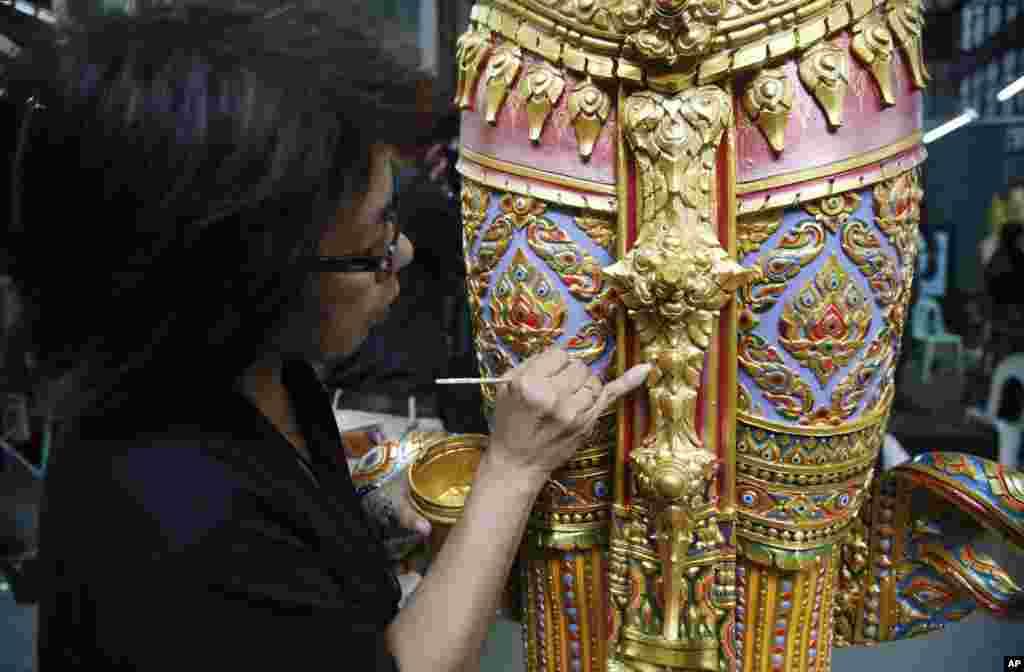 Seorang seniman melukis patung malaikat yang sedang berdiri dari epik India kuno untuk dekorasi kremasi kerajaan di Departemen Seni di Bangkok, Thailand, 8 Agustus 2017. Persiapan-persiapan untuk pemakaman Raja Bhumibol Adulyadej hampir selesai.