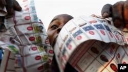ພວກສະໜັບສະໜຸນຜູ້ສະມັກປະທານາທິບໍດີຝ່າຍຄ້ານ ທ່ານ Etienne Tshisekedi ພາກັນແຫ່ສະແດງ ໃນ ອັນທີ່ພວກເຂົາເຈົ້າອ້າງວ່າເປັນສຳເນົາຂອງບັດທີ່ສໍ້ໂກງທີພົບເຫັນໃນເຂດປະຊາຄົມ Bandal ໃນນະຄອນຫຼວງ Kinshasa ໃນມື້ວັນຈັນທີ 28 ພະຈິກຜ່ານມາ (2 ທັນວາ 2011)