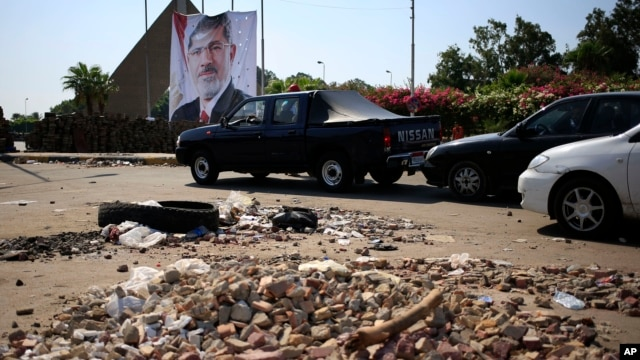 Cars drive between brick barricades erected along a street that leads to Rabaah al-Adawiya mosque, where supporters of Egypt's ousted President Mohammed Morsi have installed a camp and hold daily rallies at Nasr City, in Cairo, July 29, 2013.