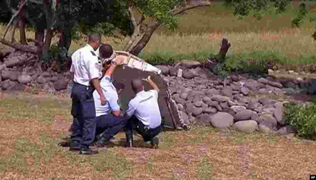 Des gendarmes et policiers français inspectent d'avion trouvé sur la plage de Saint-André, sur l'île française de l'océan Indien de la Réunion, 29 juillet 2015.