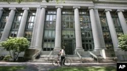 FILE - In this Aug. 1, 2005, image, a bicyclist walks by Harvard University's Langdell Hall, which includes Harvard Law School's library, in Cambridge, Mass. Following an October 2015 talk at Harvard Law School organized by students in the group Justice for Palestine, the international law firm Milbank modified a five-year, $1 million pledge to fund scholarly conferences organized by Harvard Law School students, deciding the 2012 donation from the New York City-based firm should no longer pay for student activities.