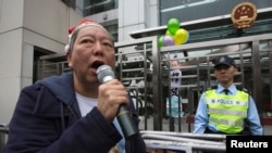 FILE - Pro-democracy lawmaker Lee Cheuk-yan speaks after releasing balloons with caricatures of jailed Chinese Nobel Peace Prize laureate Liu Xiaobo during a protest outside the Chinese liaison office in Hong Kong.