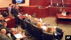 FILE - In this image taken from video, accused Colorado theater shooter James Holmes, standing on the far left, listens as the verdict is read during his trial, in Centennial, Colorado, July 16, 2015.