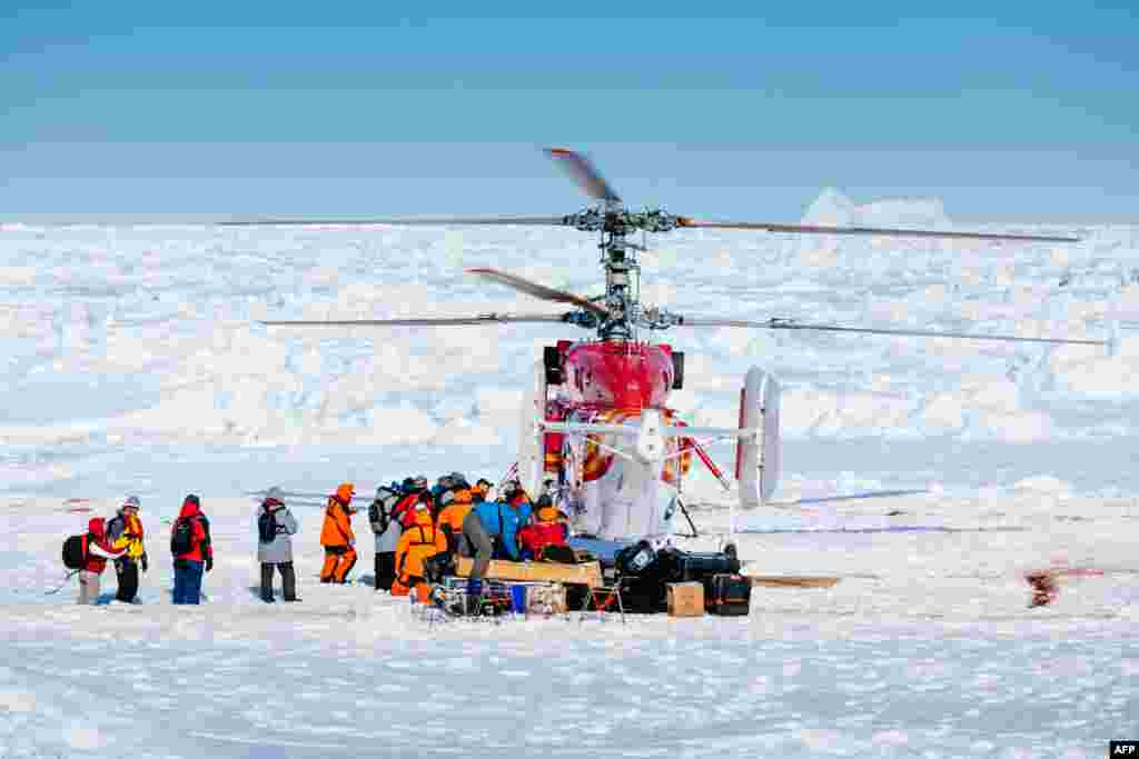This image taken by expedition doctor Andrew Peacock of www.footloosefotography.com shows a helicopter from the nearby Chinese icebreaker Xue Long picking up the first batch of passengers from the stranded Russian ship MV Akademik Shokalskiy in Antarctica.