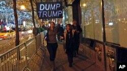 """Unas manifestantes protestan por la presencia de Donald Trump en el probrama Saturday Night Live, con un letrero que dice """"Boten a Trump""""."""