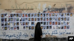 FILE - A Bahraini woman walks past images of political prisoners plastered on a wall in Sanabis, Bahrain, Oct. 22, 2015,