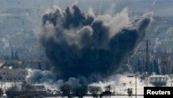 Asap hitam terlihat membumbung di kota Kobani, Suriah, menyusul serangan udara pasukan koalisi di wilayah itu (28/10).