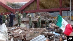 FILE - Soldiers remove debris from a partly collapsed municipal building felled by a massive earthquake in Juchitan, Oaxaca state, Mexico, Sept. 8, 2017.