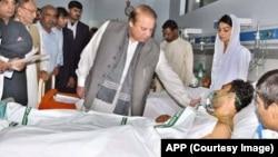 PM Nawaz Sharif (tengah) mengunjungi para korban serangan bom di Lahore yang dirawat di rumah sakit, Senin (28/3) pagi.