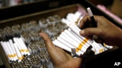 An employee counts cigarettes before packing them in Sidoarjo, Indonesia's East Java province April 7, 2010.