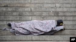 Seorang tunawisma tidur di luar tangga Katedral di tengah wabah virus corona di Sao Paulo, Brazil, 7 Mei 2020.