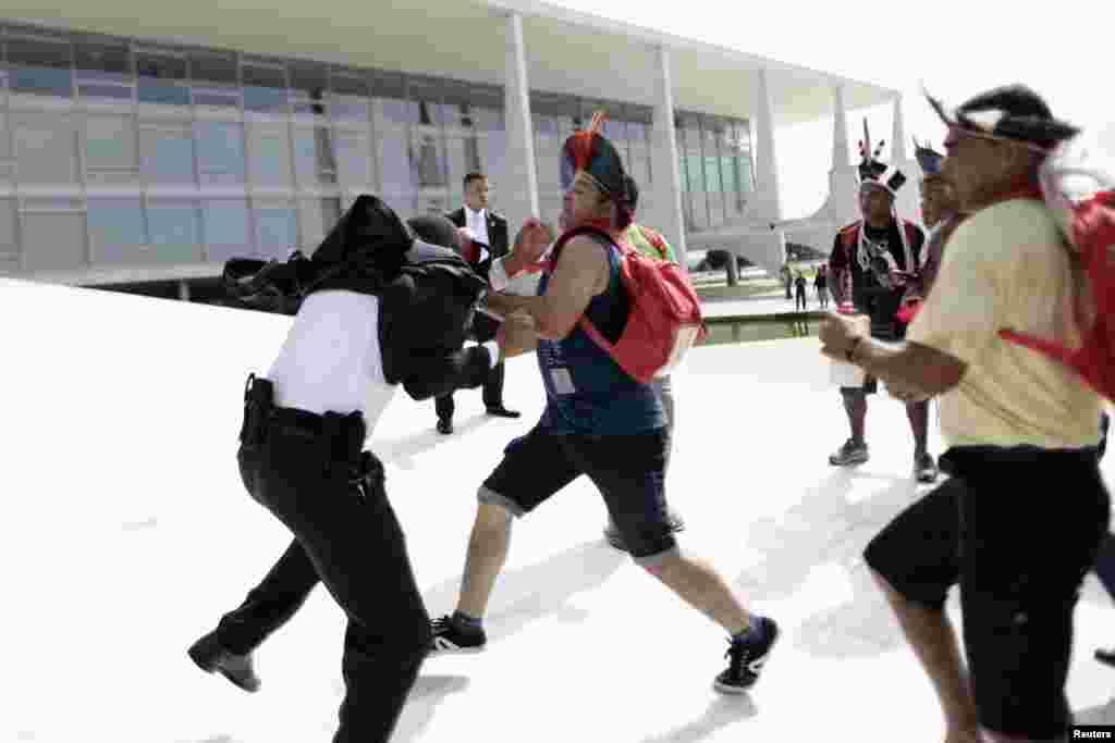 Thổ dân đụng độ với lính gác trong một cuộc biểu tình phản đối việc phân định đất của người bản địa tại Cung điện Planalto ở Brasilia, Brazil.