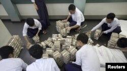 ရန္ကုန္ၿမိဳ႕က ဘဏ္တခုမွာ ၀န္ထမ္းေတြ ေငြေရတြက္။ (ဓာတ္ပံု Reuters / Minzayar )