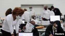 密歇根州底特律市一处投票站的工作人员在整理选票。(2020年11月3日)