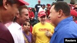 El presidente Hugo Chávez (derecha) conversa con el actor estadounidense Sean Penn durante un mitín en Valencia, unos 150 kilómetros al occidente de Caracas, el domingo 5 de agosto de 2012.