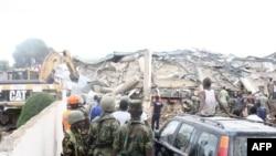 人们注视推土机清理倒塌商场瓦砾