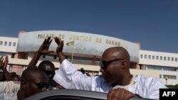 Le député socialiste sénégalais et membre de la coalition au pouvoir, Barthélemy Dias, salue les sympathisants alors qu'il quitte le palais de justice de Dakar le 1er décembre 2016.