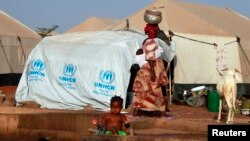 A woman walks past a child playing with water in a refugee camp in Sevare, Mali, Jan. 26, 2013.