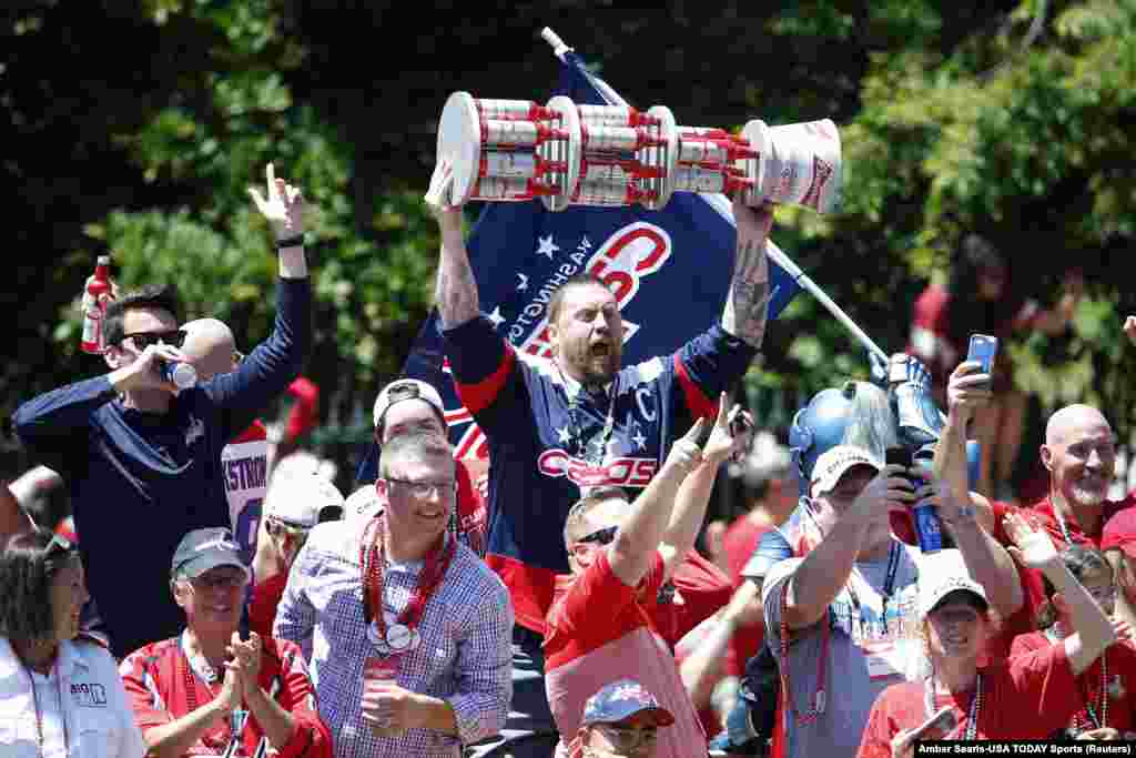 Washington Capitals fans cheer from the bus ridding in the Stanley Cup championship parade and celebration on Constitution Avenue.