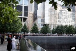 Pope Francis and Cardinal Timothy Dolan, left, pray at the South Pool of the 9/11 Memorial in New York City, Sept. 25, 2015.