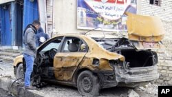 一名巴格达居民查看自己那辆在2月23日爆炸案中被炸毁的汽车
